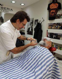 Moisés arreglando una barba en su barbería Haircuts & Wines